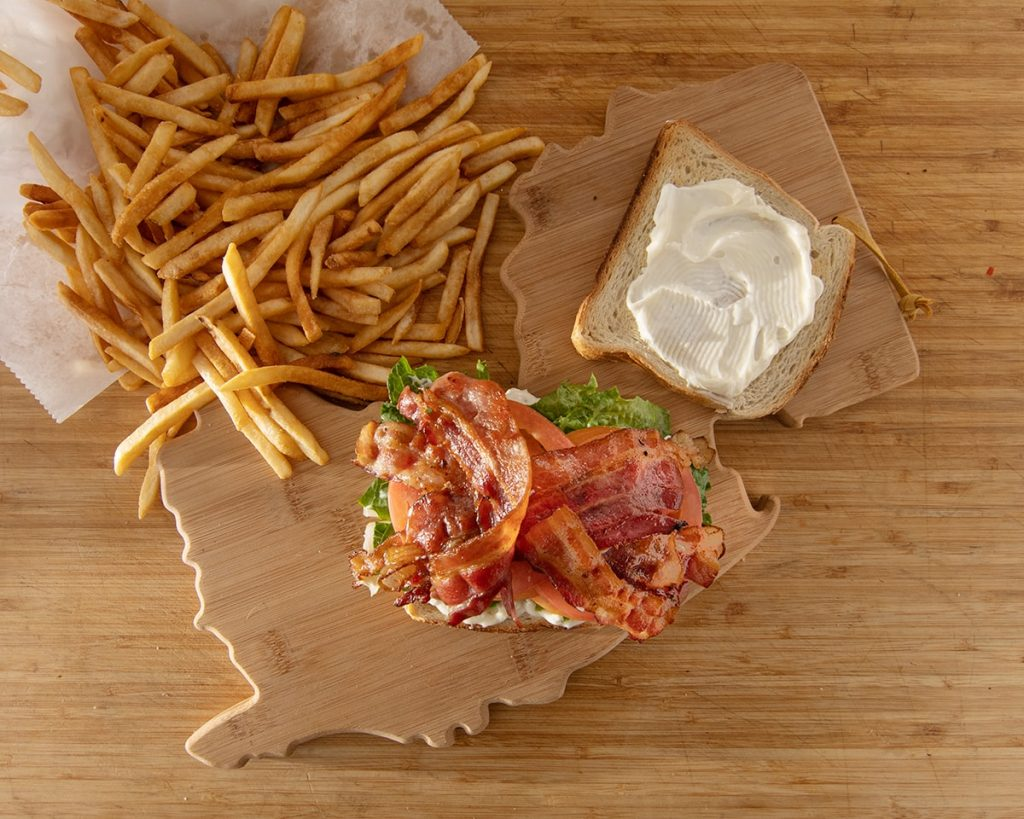 bacon lettuce tomato sandwich on a toasted bread with cream cheese. next to it are fries. all on a wooden new jersey tray on a wooden table.