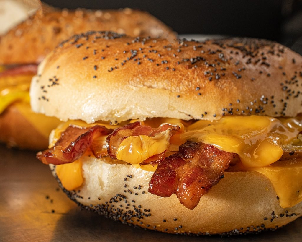a close up of a bacon, egg and cheese poppy seed bagel.