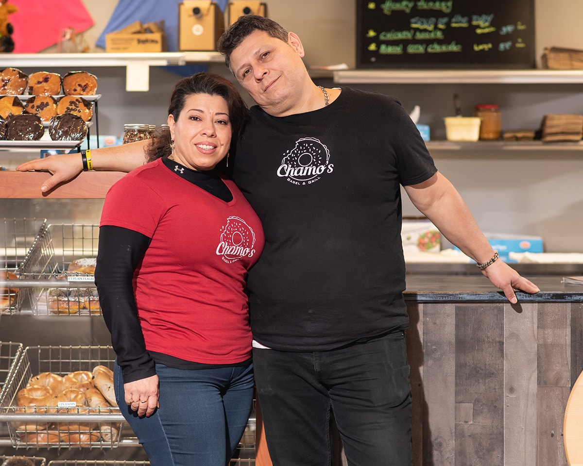 The owners of Chamos Bgael and gril are smiling in front of the counter where you can see bagels on the left side.
